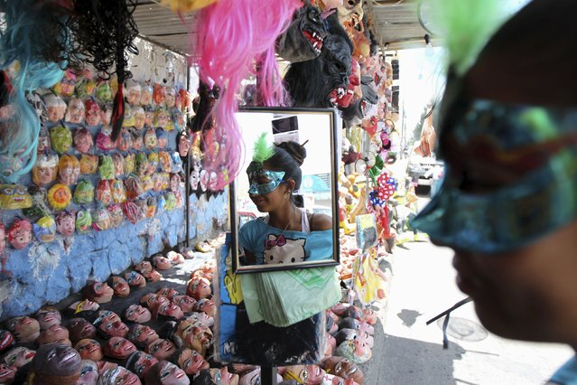A woman wears a mask at a stall in preparation for New Year's eve in Quito December 30, 2015. (Photo by Guillermo Granja/Reuters)