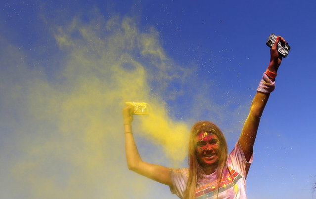 A woman throws yellow powder in the air after finishing the Colour Run at Centennial Park in Sydney August 25, 2013. According to organizers, 15,000 runners registered to complete the 5km (3 miles) course in Centennial Park on Sunday, being covered in blue, pink, orange and yellow powder on their way to the finish line. (Photo by Daniel Munoz/Reuters)
