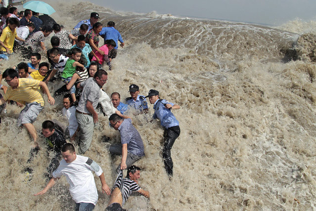 Policemen and residents run as waves from a tidal bore surge past a barrier on the banks of Qiantang River in Haining, Zhejiang province August 31, 2011. As Typhoon Nanmadol approaches eastern China, the tides and waves in Qiantang River recorded its highest level in 10 years, local media reported. (Photo by Reuters/China Daily)