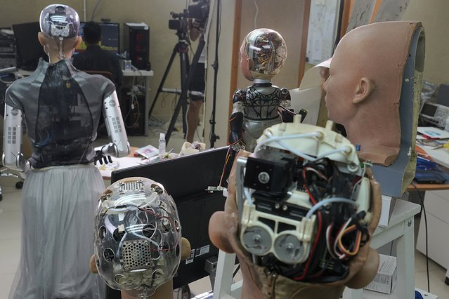 The head of Sophia, left, and other robotics show the inside content visually through the transparent skull at Hanson Robotics studio in Hong Kong on March 29, 2021. (Photo by Vincent Yu/AP Photo)