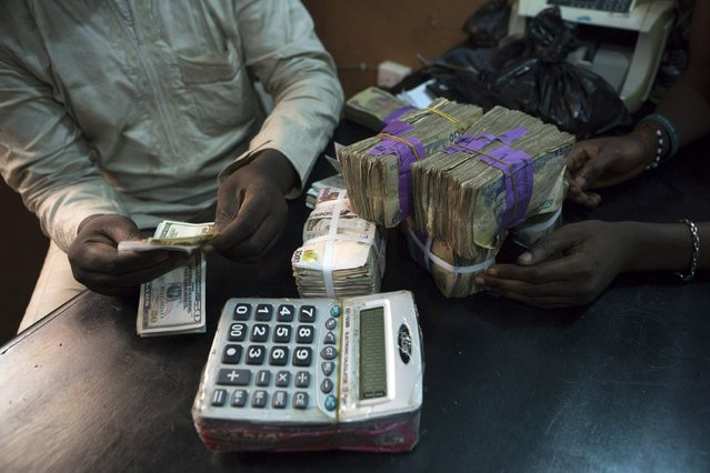 A trader changes dollars with naira at a currency exchange store in Lagos February 12, 2015. Electronic trading in Nigeria's naira was halted for the second day running on Thursday as the currency of Africa's biggest economy continued to crumple due to weak oil prices and escalating tension over this week's delayed election. (Photo by Joe Penney/Reuters)