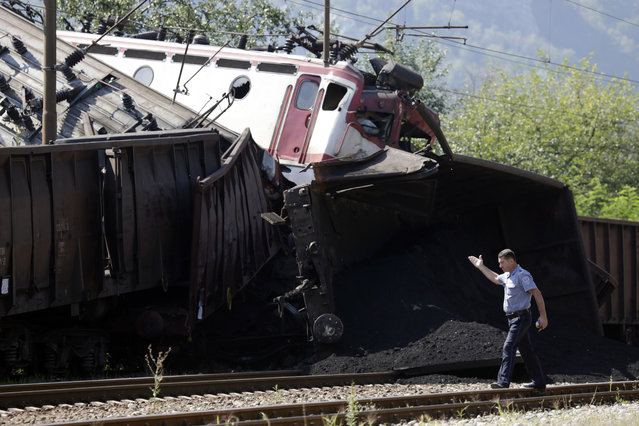 A police officer walks near the site where two cargo trains collided at the train station in Jablanica, about 80 kms south of Sarajevo, Bosnia, Thursday, August 23, 2018. Police say two people have been killed and one was seriously injured in a head-on freight train collision in southern Bosnia, early Thursday. (Photo by Amel Emric/AP Photo)