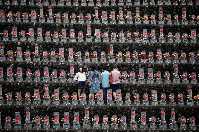 In this picture taken on August 13, 2018 a family pays respects in front of jizo statues in Jizoji Buddhist Temple in Oganomachi, Saitama prefecture, for the souls of unborn children and those who died at a young age, during the Obon prayers period. The Jizoji temple in Ogano, northwest of Tokyo, enshrines some 15,000 jizo stone statues dedicated for the souls of those who died at a young age, including miscarried and aborted babies. Hundreds of the temple's followers and those who have donated the stone statues gather for the Obon prayer on August 13, one of the days the souls of the dead are believed to return to the world under the Buddhist teaching. (Photo by Behrouz Mehri/AFP Photo)