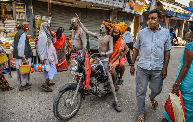 Indian holy men, or Naga Sadhu, ride a motorbike on their way to take a holy dip in the Ganges River during the Kumbh Mela at Haridwar, Uttarakhand, India, 14 April 2021. Thousands of pilgrims gather for the mass Hindu pilgrimage which occurs every twelve years and rotates among four locations. (Photo by Idrees Mohammed/EPA/EFE)