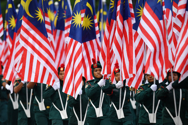 Malaysian school cadets carry national flags during the National Day celebration parade in Putrajaya, on the outskirts of Kuala Lumpur on August 31, 2018. (Photo by Manan Vatsyayana/AFP Photo)