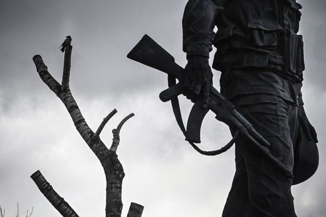 A bird sits on a tree next to a monument to Soviet soldiers killed in action in Afghanistan during Soviet invasion of 1979-1989 at Moscow's Poklonnaya Hill War Memorial Park on April 2, 2021. For the decade a total of 620,000 Soviet soldiers served with the forces in Afghanistan. The total irrecoverable personnel losses of the Soviet Armed Forces amounted about to 15,000. (Photo by Alexander Nemenov/AFP Photo)