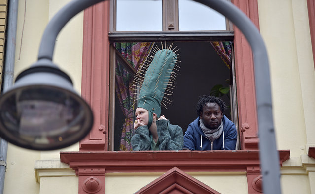 Revelers watching the traditional carnival parade from a window in Cologne, western Germany, Monday, February 16, 2015. (Photo by Martin Meissner/AP Photo)
