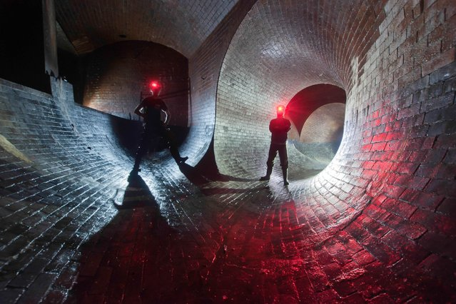 """Two urban explorers with their headtorches set to red-beam inside the River Effra, another of London's """"lost rivers"""", in London. (Photo by Bradley L. Garrett/Barcroft Media)"""