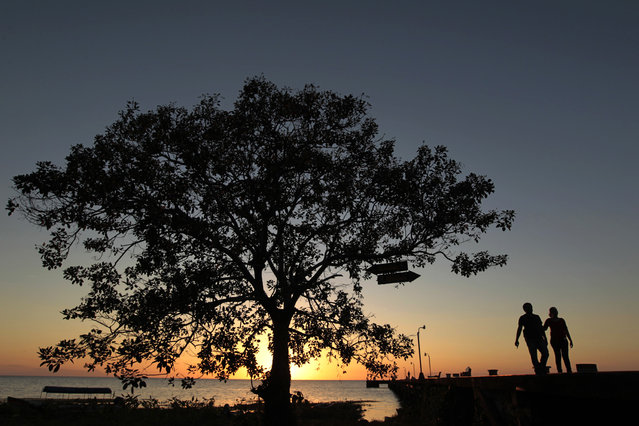A couple walks on the jetty of San Miguelito town, Nicaragua during sunset February 9, 2015. (Photo by Oswaldo Rivas/Reuters)