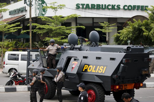 Indonesian policemen with weapons and an armoured vehicle guard in front of a Starbuck cafe at Thamrin business district in Jakarta, January 14, 2016. (Photo by Reuters/Beawiharta)