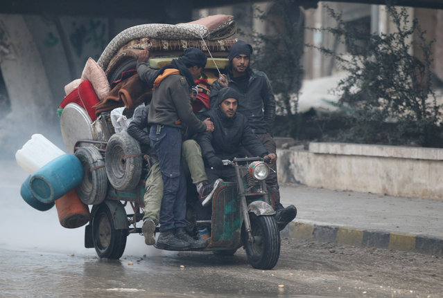 Men ride a tricycle as they flee deeper into the remaining rebel-held areas of Aleppo, Syria December 7, 2016. (Photo by Abdalrhman Ismail/Reuters)