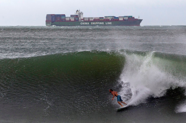 A surfer takes advantage of large waves caused by hurricane Irina which is sitting some 200 nautical miles (370 km) off Durban, March 5, 2012. (Photo by Rogan Ward/Reuters)