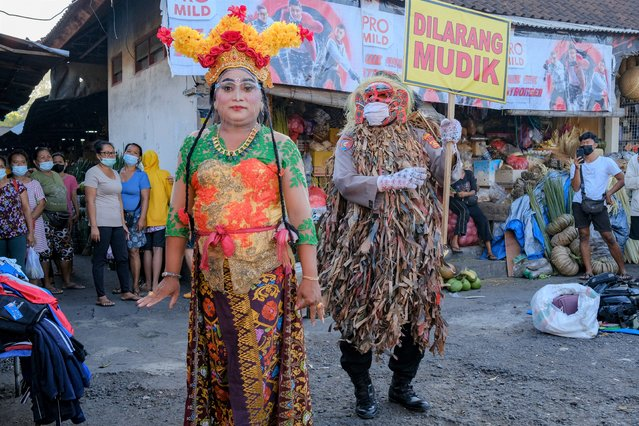 A police officer wears a Balinese traditional scary mask, locally known as Celuluk, as a traditional dancer educates people on the prevention of COVID-19 in Bali, Indonesia, 11 May 2021. Local police officers are using Balinese traditional characters to attract public attention in an attempt to provide education on COVID-19. (Photo by Made Nagi/EPA/EFE)