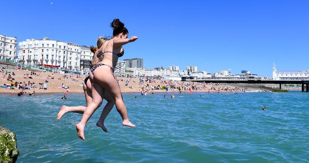 Swimmers cool off and jump into the sea whilst enjoying the hot weather and as sunworshippers cram onto Brighton beach in sizzling 78F heat on the warmest day of the year in the United Kingdom on June 1, 2021. (Photo by Anthony Harvey/Rex Features/Shutterstock)