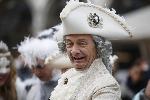A man impersonating Giacomo Casanova smiles in St. Marks' Square, during the Carnival, in Venice, Italy, Sunday, January 24, 2016. Authorities have increased surveillance throughout the city and increased the number of officers on patrol, both under-cover and in uniform, but backed down on a proposal to ban revelers from wearing masks on the occasion of the Venice Carnival. (Photo by Luca Bruno/AP Photo)