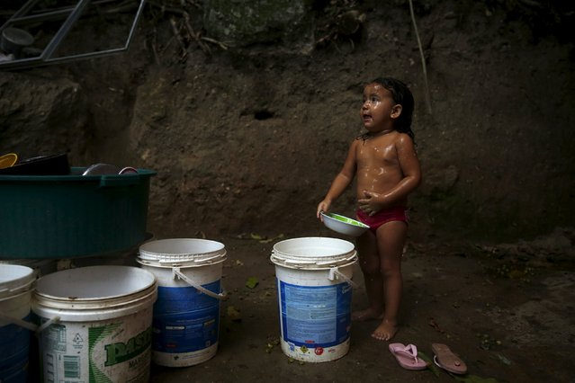 A child takes a bath with buckets of water at her home in the Rocinha slum in Rio de Janeiro, March 19, 2015. The International Water Day is held on March 22. (Photo by Pilar Olivares/Reuters)
