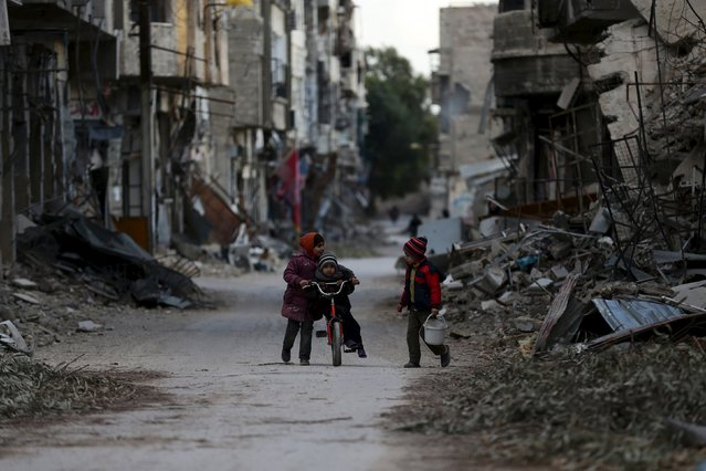 A girl pushes a boy on a bicycle past damaged buildings in Jobar, a suburb of Damascus, Syria January 23, 2016. (Photo by Bassam Khabieh/Reuters)