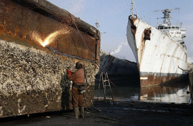 A worker uses a cutting torch to dismantle the hull of a barge covered in barnacles near French navy vessels at the Galloo ship recycling plant in Ghent March 24, 2015. The site, which is Europe's largest ship recycling plant processes some 35,000 tonnes of metal every year. (Photo by Francois Lenoir/Reuters)
