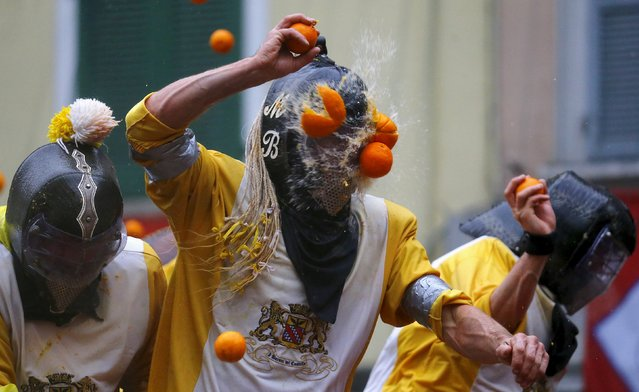 "A participant is hit by an orange during an annual carnival battle in the northern Italian town of Ivrea February 7, 2016. Dressed up as Middle Age kings' guards, a group of men ride in a horse-drawn carriage and pelt ""foot soldiers"" with oranges as thousands of people gather to re-enact a Middle Age battle when the townsfolk of Ivrea overthrew an evil king. In a strange twist, instead of swords and cross bows, these days the weapons of choice are oranges. (Photo by Stefano Rellandini/Reuters)"