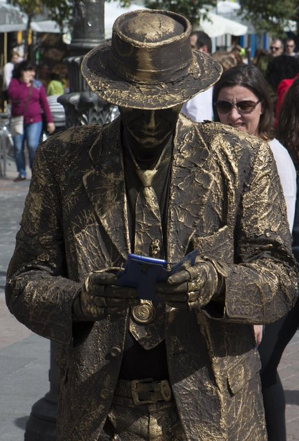 A human statue street artist takes a break to look at his cellphone in Madrid, Spain, Sunday, March 29, 2015. (Photo by Paul White/AP Photo)