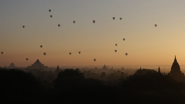 Balloons carrying visitors fly over old temples at sunrise Tuesday, December 27, 2016 in Bagan, Nyaung U district, central Myanmar. (Photo by Thein Zaw/AP Photo)