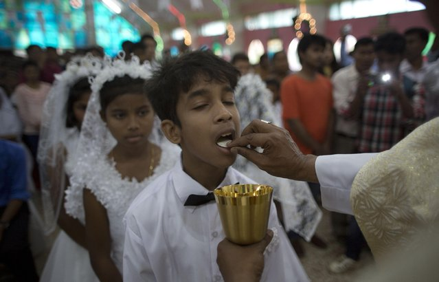 Young Indian Christians receive holy communion from a priest during Easter mass at a Church in Gauhati, India, Sunday, April 5, 2015. (Photo by Anupam Nath/AP Photo)