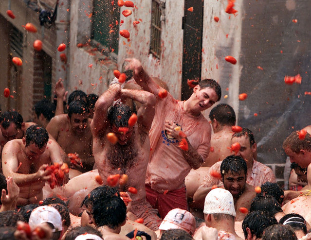 Festival revelers engage in the annual Tomatina tomato fight in Bunyol, eastern Spain, August 2000. (Photo by Desmond Boylan/Reuters)