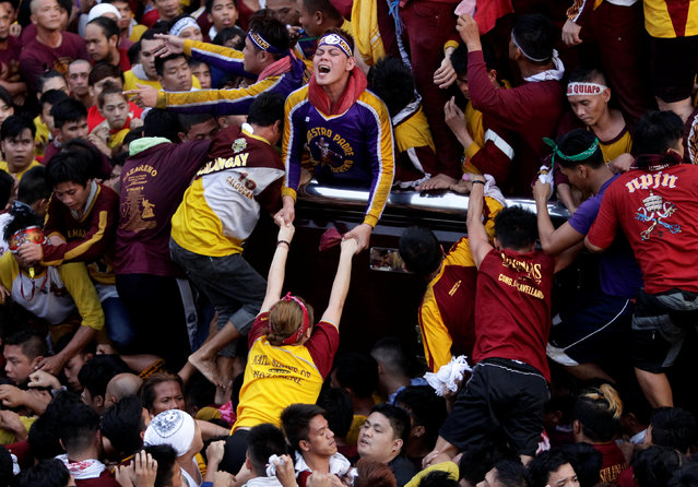 A man pulls a devotee as they try to touch the statue of the Black Nazarene during its annual procession in Manila, Philippines January 9, 2017. (Photo by Czar Dancel/Reuters)