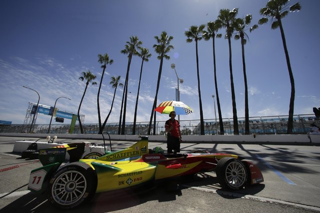Crew member Dennis Scherbaum, of Germany, holds an umbrella for race car driver Lucas di Grassi before a qualifying session of the Formula E Long Beach ePrix auto race, Saturday, April 4, 2015, in Long Beach, Calif. (Photo by Jae C. Hong/AP Photo)