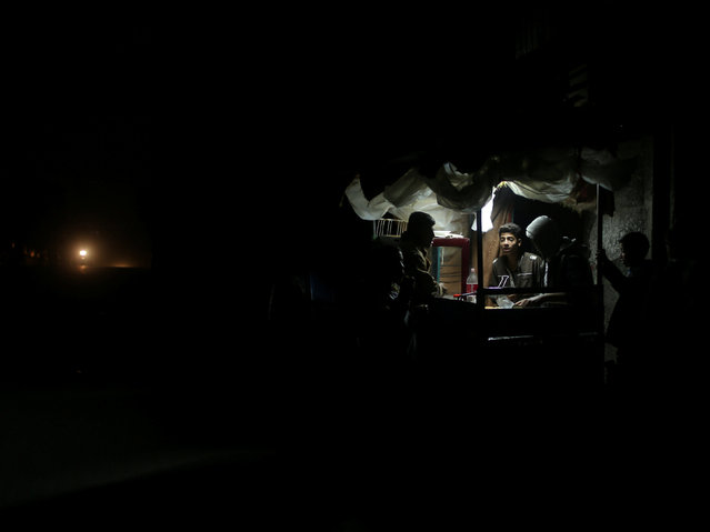 A Palestinian man sells falafel in a makeshift shop lit with a lamp powered by a battery during a power cut in Beit Lahiya in the northern Gaza Strip January 11, 2017. (Photo by Mohammed Salem/Reuters)
