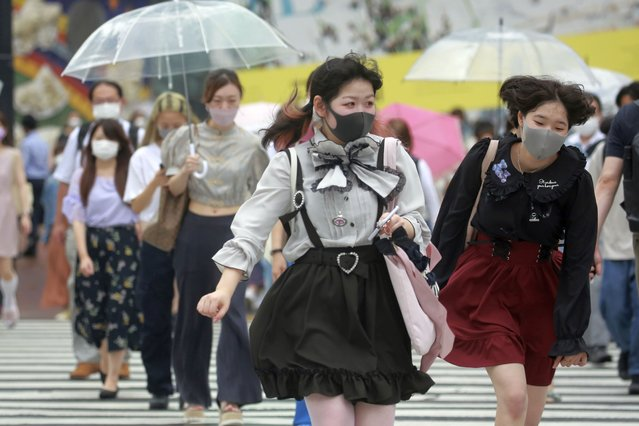 People wearing face masks to protect against the spread of the coronavirus walk on a crossing in Tokyo Tuesday, August 17, 2021. Japan's coronavirus state of emergency will continue through Sept. 12 rather than finishing at the end of this month as initially planned, the government decided Monday. (Photo by Koji Sasahara/AP Photo)
