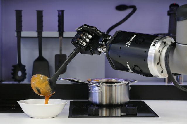 A robot in the Robotic Kitchen prototype created by Moley Robotics cooks a crab  soup at the company's booth at the world's largest industrial technology fair, the Hannover Messe, in Hanover April 13, 2015. (Photo by Wolfgang Rattay/Reuters)