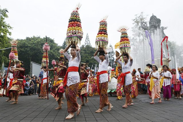 Balinese perform as they take part in a cultural parade during a New Year's Eve celebration at a main road in Denpasar, Bali, Indonesia, 31 December 2013. (Photo by Made Nagi/EPA)