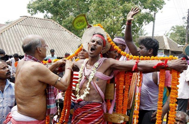A Hindu devotee reacts as a nail is pierced through his arm skin during the annual Shiva Gajan religious festival in Batanal village, east of Kolkata, April 14, 2015. (Photo by Rupak De Chowdhuri/Reuters)