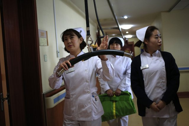 Nurses demonstrate how to use a device that helps the mobility of elderly patients, at the Yanda Hospital, Sanhe City, Langfang, Hebei Province of China, 23 February 2016. The privately owned Yanda hospital, situated 34 kilometres east of Beijing city, is part of a co-ordinated development plan for the Beijing-Tianjin-Hebei area. Medical experts, doctors, and nurses, from major hospitals of Beijing city will colaborate to improve medical services and health care in Hospitals outside of the city. (Photo by How Hwee Young/EPA)