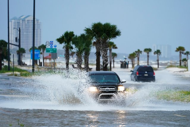 Cars drive through flood waters along route 90 as outer bands of Hurricane Ida arrive Sunday, August 29, 2021, in Gulfport, Miss. (Photo by Steve Helber/AP Photo)
