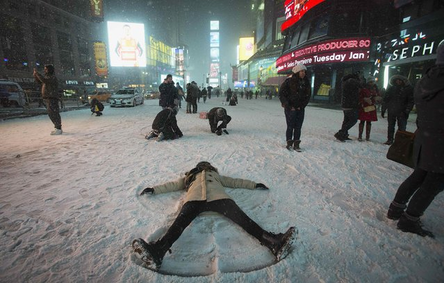 A woman makes a snow angel in the middle of Times Square in New York, January 3, 2014. The governors of New York and New Jersey declared a state of emergency and urged residents to stay indoors as a major storm, called Hercules by local media, hit the northeastern United States on Thursday, bringing heavy snow and delaying or cancelling thousands of flights. (Photo by Carlo Allegri/Reuters)