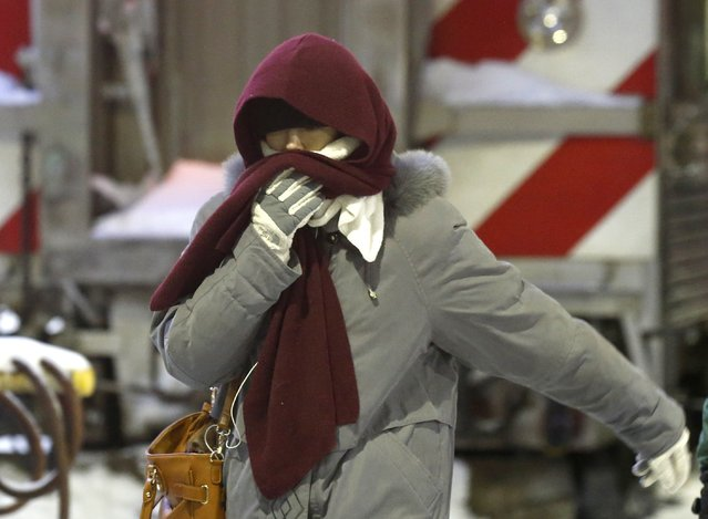 A woman walks briskly as she arrives at the La Salle Street commuter rail station with temperatures well below zero and wind chills expected to reach 40 to 50 below, Monday, January 6, 2014, in Chicago. (Photo by Charles Rex Arbogast/AP Photo)