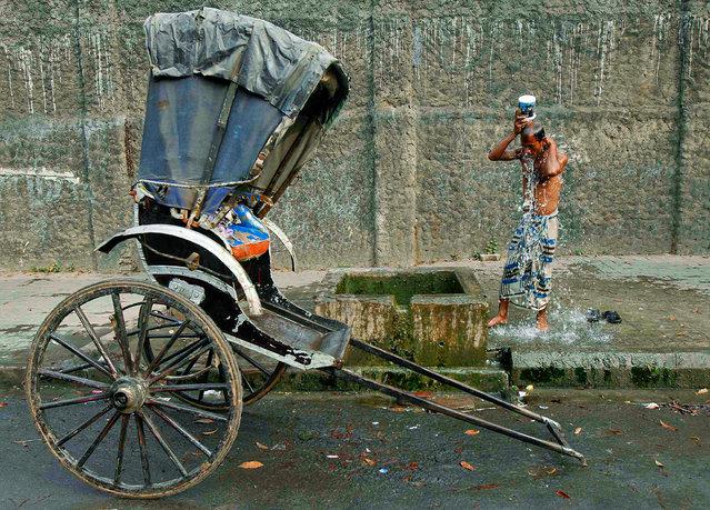 A rickshaw puller baths by the roadside on a winter morning in Kolkata January 7, 2014. (Photo by Rupak De Chowdhuri/Reuters)