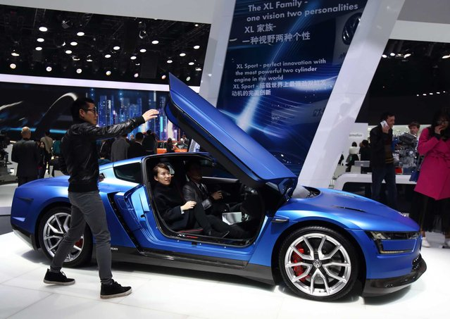 Visitors try a Volkswagen AG XL vehicle at the 16th Shanghai International Automobile Industry Exhibition (Auto Shanghai 2015) in Shanghai, China, on Monday, April 20, 2015. (Photo by Tomohiro Ohsumi/Bloomberg)