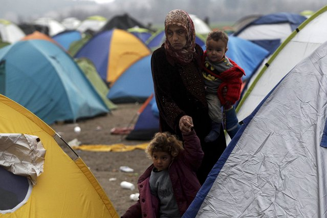 A refugee holding two children walks among tents at a makeshift camp set up by stranded refugees and migrants who are waiting to cross the Greek-Macedonian border, near the Greek village of Idomeni, February 29, 2016. (Photo by Alexandros Avramidis/Reuters)