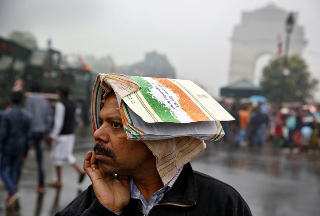 A man shelters from the rain at the India Gate following the Republic Day parade in New Delhi, India January 26, 2017. (Photo by Cathal McNaughton/Reuters)