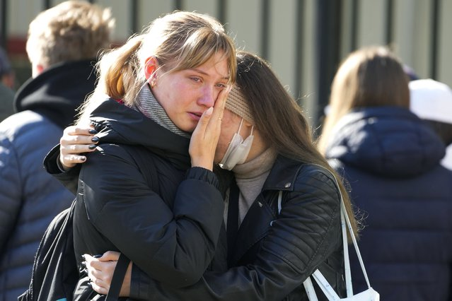 Students comfort each other as they gather outside the Perm State University following a campus shooting in Perm, about 1,100 kilometers (700 miles) east of Moscow, Russia, Tuesday, September 21, 2021. (Photo by Dmitri Lovetsky/AP Photo)