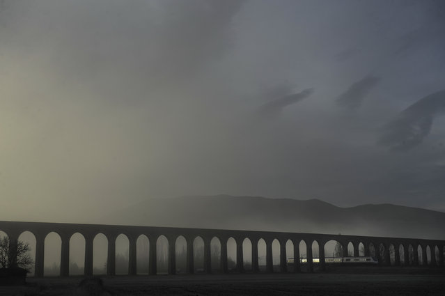 The fog covers the landscape while a train crosses an ancient aqueduct, bottom right, in Noain northern Spain, Monday, December 30, 2013. (Photo by Alvaro Barrientos/AP Photo)