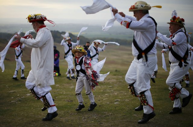 A boy dances with Leicester Morrismen dance during May Day celebrations at Bradgate Park in Newtown Linford, Britain May 1, 2015. (Photo by Darren Staples/Reuters)