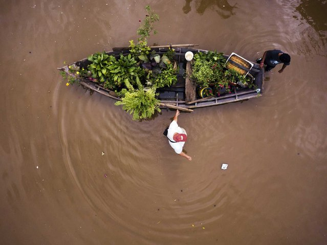 People transport their plants in a boat through a flooded street in the Jukyty neighborhood, in Asuncion, Paraguay, Thursday, April 4, 2019. More than 20,000 people in Paraguay have been evacuated after torrential rains caused extensive flooding. (Photo by Jorge Saenz/AP Photo)
