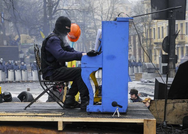 An opposition supporter plays the piano on barricades in front of riot police in central Kiev, Ukraine, on February 10, 2014. The country has been rocked by nearly three months of anti-government protests sparked by President Viktor Yanukovich's refusal to sign a wide-ranging trade agreement with the European Union. (Photo by Efrem Lukatsky/Associated Press)