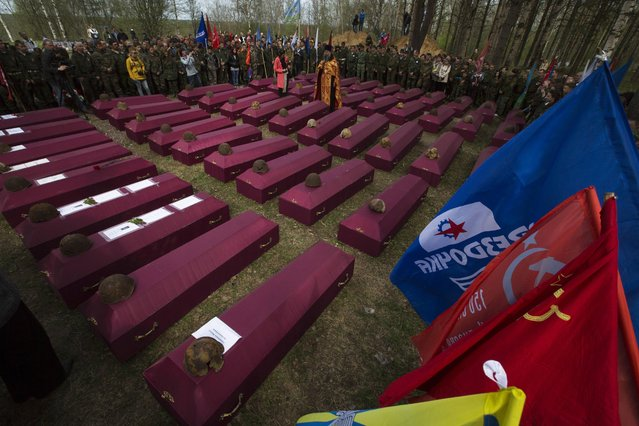 In this photo taken Thursday, May 7, 2015 photo, an Orthodox priest conducts a reburial ceremony of remains of Soviet soldiers killed during World War II, at the Sinyavino Heights memorial near the village of Sinyavino, 50 km (31 miles) east of  St. Petersburg, Russia. (Photo by Dmitry Lovetsky/AP Photo)