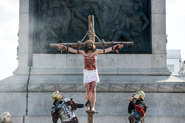 "Actor James Burke-Dunsmore stands on a crucifix whilst playing Jesus during The Wintershall's ""The Passion of Jesus"" in front of crowds on Good Friday at Trafalgar Square on March 25, 2016 in London, England. (Photo by Chris Ratcliffe/Getty Images)"