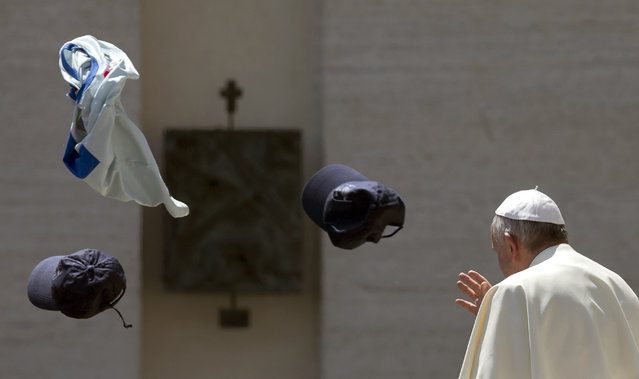 Faithful throw in the air a jersey and two hats as Pope Francis leaves at the end of his weekly general audience in St. Peter's Square at the Vatican, Wednesday, May 13, 2015. (Photo by Alessandra Tarantino/AP Photo)
